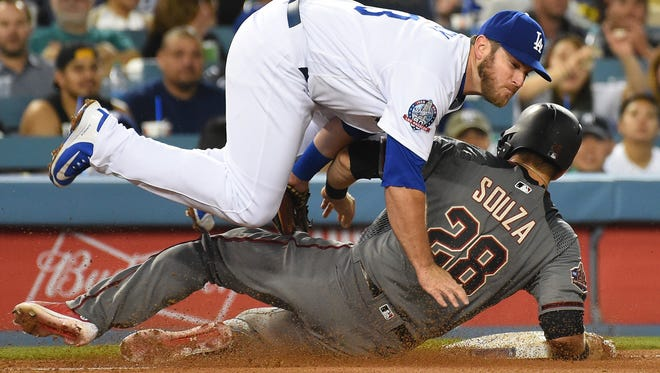 May 8, 2018: Los Angeles Dodgers first baseman Max Muncy (13) is upended by Arizona Diamondbacks right fielder Steven Souza Jr. (28) as he is out at third on a double steal attempt in the fifth inning of the game at Dodger Stadium.