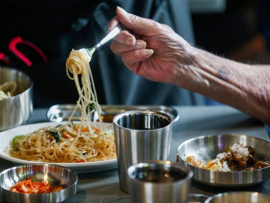 A customer takes some noodles with vegetables at Bawi during a special event for Korean War veterans at the new all-you-can-eat Korean barbecue restaurant located at 4121 S. National Ave.