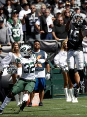 Oakland Raiders wide receiver Michael Crabtree (15) catches a touchdown pass against New York Jets cornerback Juston Burris (32) during the first half of an NFL football game in Oakland, Calif., Sunday, Sept. 17, 2017. (AP Photo/Marcio Jose Sanchez)