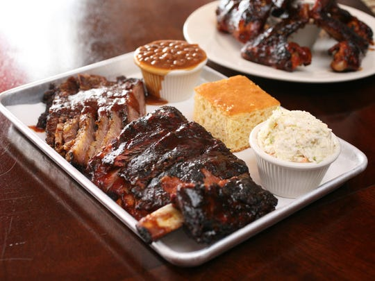 A combination plate with brisket and ribs, cornbread, baked beans and coleslaw, and a plate of wings at Q Restaurant in Port Chester.