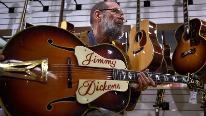 George Gruhn holds a Gibson Super 400 guitar that belonged to Little Jimmy Dickens at his Gruhn Guitars on Wednesday, Dec. 16, 2015, in Nashville. Gruhn is selling 18 guitars for the Dickens estate.