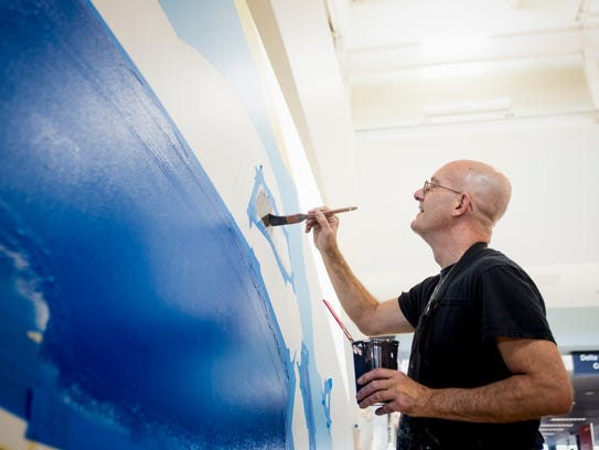 Kevin T. Kelly paints the windows of the airplane featured