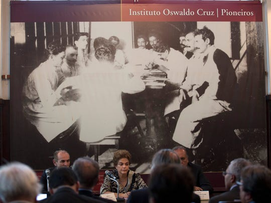 Brazil's President Dilma Rousseff, sitting center, attends a meeting at the Fiocruz research institute in Rio de Janeiro, Brazil, Thursday, March 10, 2016. Brazil's Health Minister Marcelo Castro said the country's top biomedical research institute is getting $2.8 million to fund studies aimed at combating the Zika virus. Castro also said over a $1 million will help finance a study to find a vaccine for the virus, which Brazilian researchers have tentatively linked to a surge in cases of microcephaly, a birth defect that affects infants' skulls and brains.
