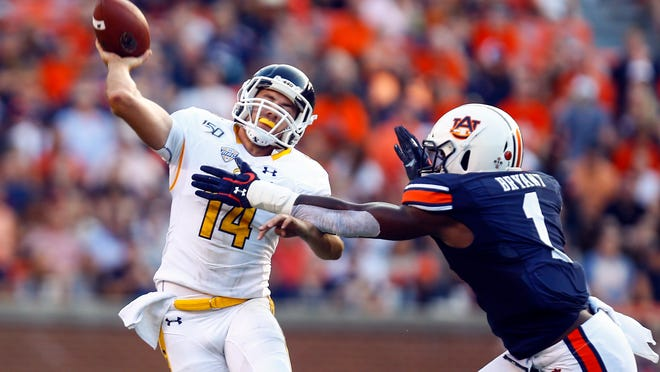 Kent State quarterback Dustin Crum gets off a pass while pressured by Auburn defensive end Big Kat Bryant during a game played last September in Alabama.