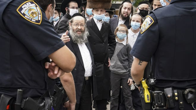 Members of the Orthodox Jewish community speak with NYPD officers on a street corner Oct. 7 in the Borough Park neighborhood of the Brooklyn borough of New York. Gov. Andrew Cuomo moved to reinstate restrictions on businesses, houses of worship and schools in and near areas where coronavirus cases are spiking. Many neighborhoods that stand to be affected are home to large enclaves of Orthodox Jews.