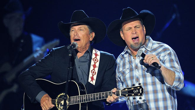 George Strait, left, and Garth Brooks perform together during the 48th Annual ACM Awards show at the MGM Grand Garden Arena in Las Vegas April 7, 2013.