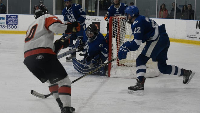 Brother Rice forward Nick Marone (10) fires a shot at Notre Dame Academy goalie Bo Buckely as defenseman Logan Braun moves in to cover a rebound.