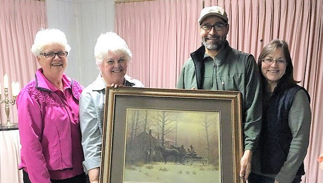 Ruidoso Federated Woman's Club members Annette Cooke and Sally Moore delivered the signed and numbered G. Harvey print to winner Rudy Valdez.