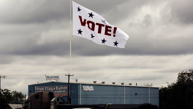 "FILE - In this Nov. 8, 2016, file photo, a huge ""Vote!"" flag waves above Interstate 35 as motorists pass, in San Antonio. Texas election officials have acknowledged that hundreds of people were allowed to bypass the state's toughest-in-the-nation voter ID law and improperly cast ballots in the November presidential election by signing a sworn statement instead of showing a photo ID. (AP Photo/Eric Gay, File)"