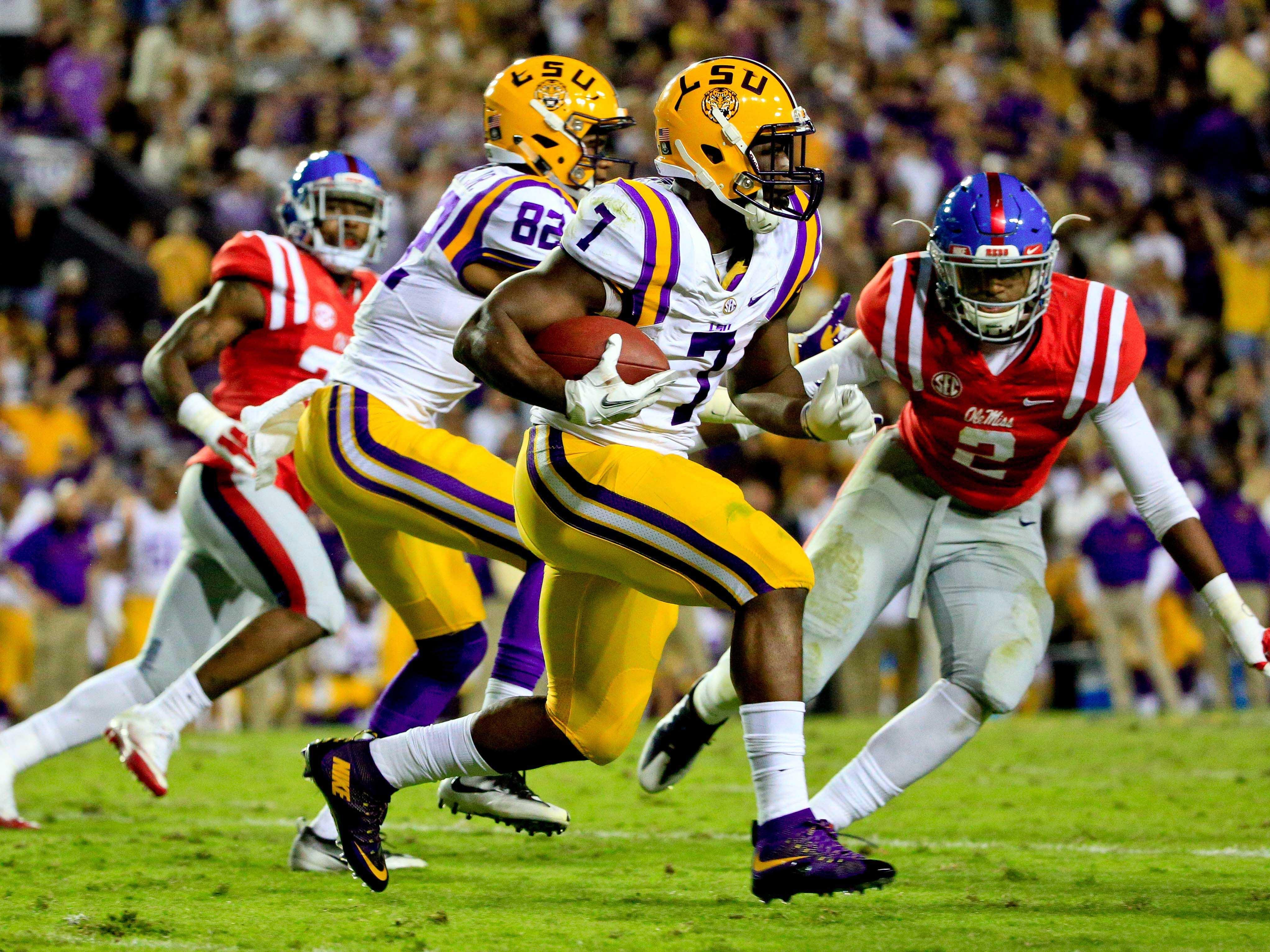 LSU Tigers running back Leonard Fournette (7) runs for a touchdown against the Ole Miss Rebels during the second quarter of a game at Tiger Stadium.