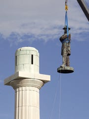 "In this May 2017 file photo, a statue of Confederate General Robert E. Lee is removed from Lee Circle in New Orleans. The city council voted to remove the monument and three other Confederate and white supremacist monuments in December 2015. A coalition of civil rights groups in Atlanta is using the 2019 Super Bowl to help kick off a renewed ""war on the Confederacy,"" in a fight to remove Confederate monuments around the nation."