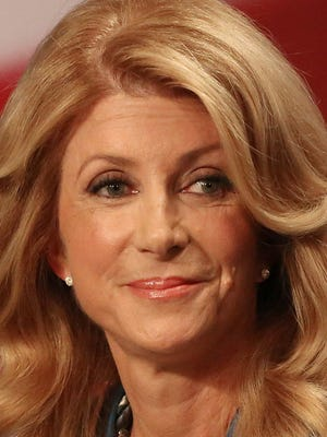 In this file photo, Texas State Senator Wendy Davis, Democratic Gubernatorial candidate, pauses before responding to a question during the final gubernatorial debate in a KERA-TV studio in Dallas on Tuesday Sept. 30, 2014. Ebola, ethics and education were among the issues that dominated the final debate between Davis and Texas Attorney General Greg Abbott.