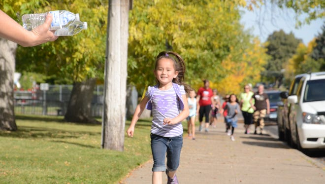 Reia Henry runs toward volunteers holding water at Lincoln Elementary School's walk-a-thon on Friday morning. Reia is a first-grader