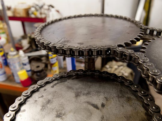 Table top made from gears and chain. Machine Brothers Mark Leonard and Dan Strode create machine age pieces from recycled and donated parts. Photo taken on Tuesday, May 26, 2015.