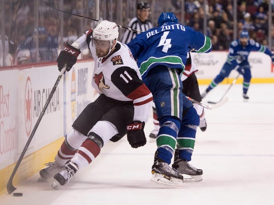 Arizona Coyotes left wing Brendan Perlini (11) gets to the puck next to Vancouver Canucks defenseman Michael del Zotto during the first period of an NHL hockey game Wednesday, March 7, 2018, in Vancouver, British Columbia. (Jonathan Hayward/The Canadian Press via AP)