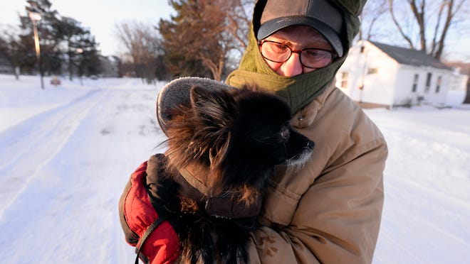 Ron Preston takes his dog Baby Girl out for a cold early morning walk in Lansing Monday after the area's heavy snowstorms.