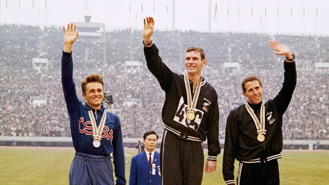 From Oct. 21, 1964, gold medalist Peter Snell, center, of New Zealand, silver medalist Josef Odlozil, left, of Czechoslovakia, and bronze medalist John Davies of New Zealand, right, stand on podium with their awards in the Olympic 1,500-meter run at the Tokyo Summer Games. The one-year postponement of the Tokyo Olympics has inspired organizers of a track meet in the Czech Republic to go ahead with their event in June. Meet director Miroslav Sevcik says the Josef Odlozil Memorial in Prague will be staged as planned on June 8, 2020 but with only 50-60 competitors because of restrictions related to the coronavirus pandemic. The meet is named after the runner who won silver in the 1,500 meters at the 1964 Tokyo Olympics.