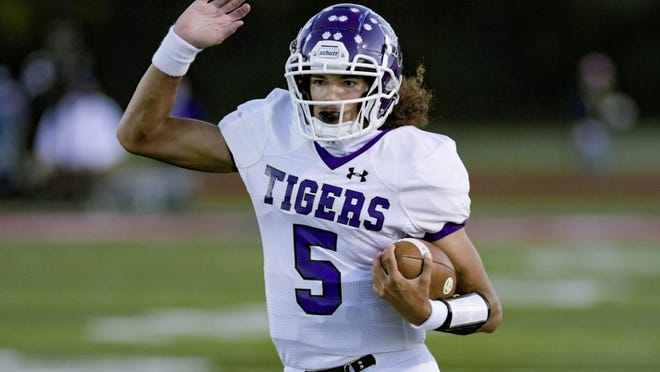 Pickerington Central's Garner Wallace finds running room against Groveport Madison's defense during the teams' game Sept. 18 at Groveport. The Tigers defeated the Cruisers 43-3.