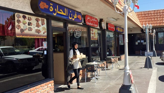 "A customer exits a Lebanese eatery in Anaheim's ""Little Arabia"" neighborhood just miles from Disneyland in Orange County. Southern California is home to the nation's largest concentration of Arab Americans."