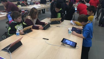 Kids check out iPads at the Apple Store in Westfield Garden State Plaza in Paramus, NJ.