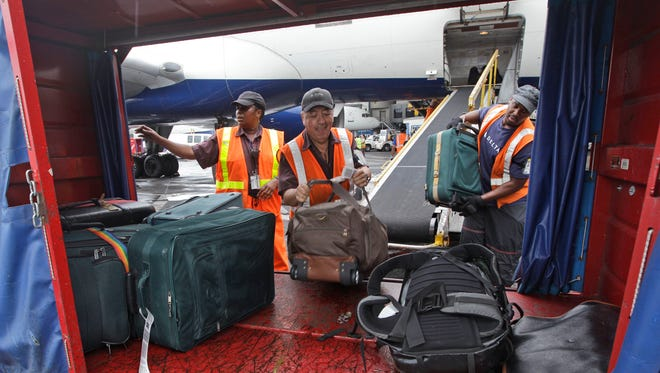 In this Wednesday, Aug. 1 2012 file photo, Delta Air Lines ramp agents unload bags from a flight arriving at JFK International airport in New York.