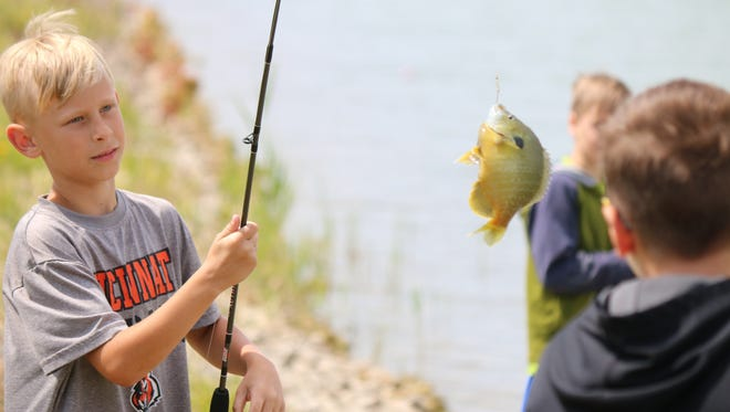 Owen Gradel, 9, catches yet another fish during the refuge ranger camp at the Ottawa National Wildlife Refuge.
