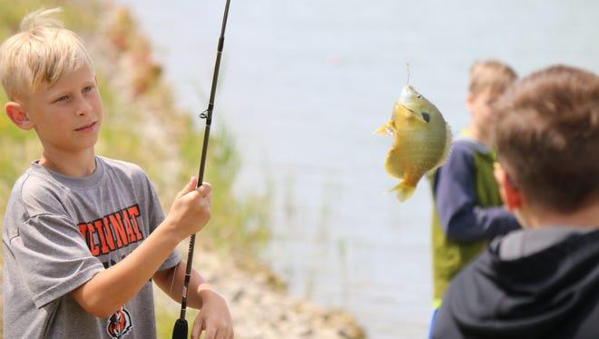 Owen Gradel, 9, catches a fish during the refuge ranger camp last summer at the Ottawa National Wildlife Refuge.