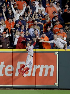 Fans interfere with Boston Red Sox right fielder Mookie Betts trying to catch a ball hit by Houston Astros' Jose Altuve during the first inning in Game 4 of the American League Championship Series on Wednesday in Houston. Altuve was called out.