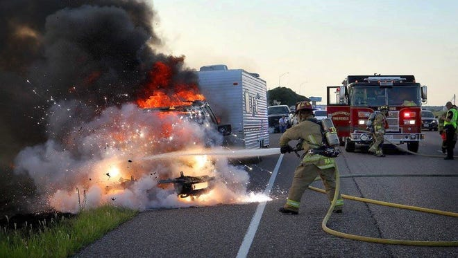 Burkburnett volunteer firefighters work to extinguish a blaze after a Ford F-150 pickup towing a camping trailer caught fire Tuesday evening on southbound I-44. No one was injured in the incident.