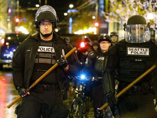 Police with wooden sticks stand guard on Dec. 8, 2014,