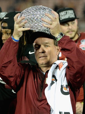 Florida State head coach Jimbo Fisher holds the Coaches' Trophy after defeating Auburn for the Seminoles' third national championship in program history.