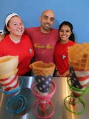 Owner Elio DeFranco with Samantha Comandini (left) and his daughter Isabella, who both work behind the counter at the ice cream shop.