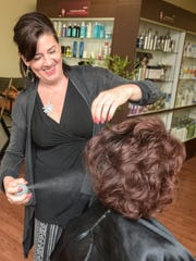 Inspirations Hair and Nail Salon in Sea Girt is co-owned by L.A. Caprioni, who is pictured here applying hair spray on a client.