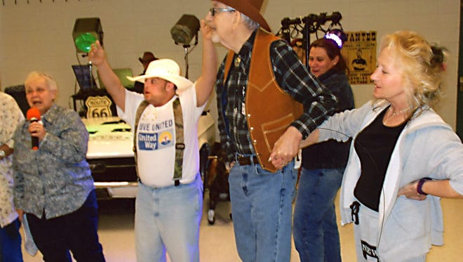 Dance participants (and caregivers) have a good time during a Western themed dance, while Dee Fluno (left) announces.