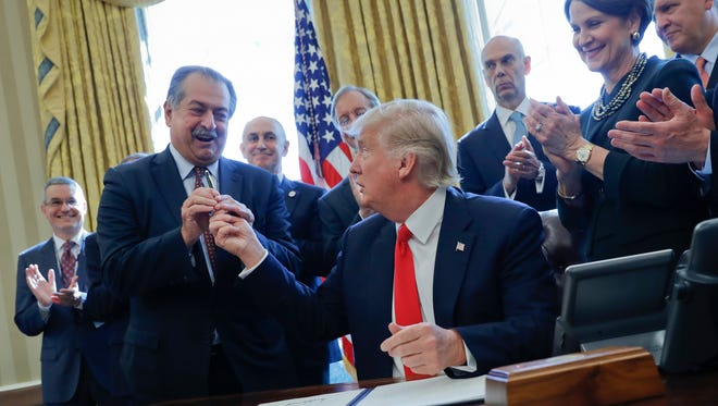 President Trump gives the pen he used to sign an executive order to Dow Chemical CEO Andrew Liveris, as other business leaders applaud in the Oval Office of the White House Feb. 24.