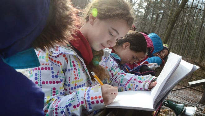 Katie Bomia, 10, and other fifth grade students from Marshall's Sherman Elementary School, write in their journals during their visit to Binder Park Zoo's Mexican grey wolf habitat on Thursday morning.