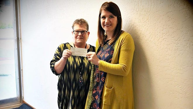 Ann Bennet, left, director of Neighbor to Neighbor, accepts check from Jenny Brandenburg, Sturgeon Bay LuLaRoe business owner.