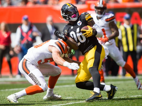 Pittsburgh Steelers running back Le'Veon Bell (26) is tackled by Cleveland Browns outside linebacker Joe Schobert (53) during the second quarter at FirstEnergy Stadium.