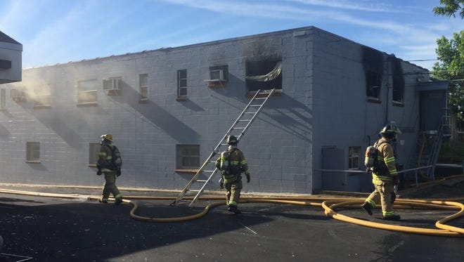 Springfield firefighters work to mitigate the effects of what appeared to be an explosion Monday morning at 1125 N. Boonville Ave. The fiery incident sprayed glass from the back windows of an apartment, which was unoccupied at the time.