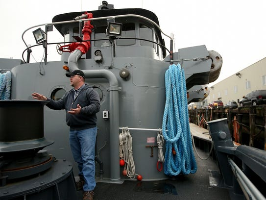 Deck hand Jason Moosmiller talks about the workings of the Navy tugboat Canonchet's capstan (to his left) and how it is used while the boat is in service at Naval Base Kitsap Bremerton.