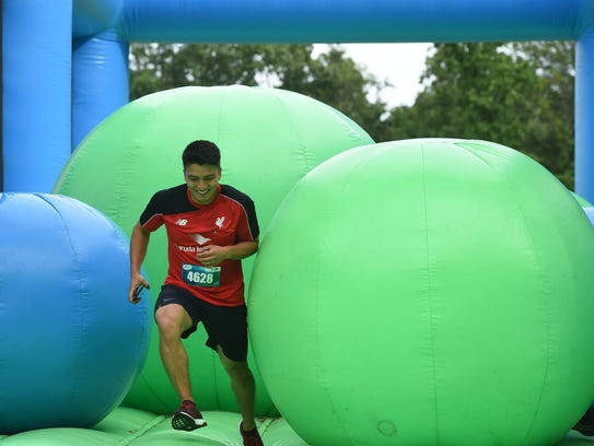 David Deleon runs through one of the inflatables during