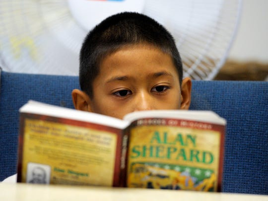Bill Bruno, not pictured, reads to Elijah Lungley, 9, pictured, and a small group of other children that are challenging their reading skills by following along and learning about heroes of history, Alan Shepard, during a week-long reading camp at Prosperity Avenue Baptist Church, Tulare.