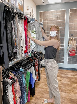 Lila Kasten, a sales associate and personal stylist, sorts through clothing at the recently reopened Style Encore, 4904 Morse Road, just north of Gahanna.