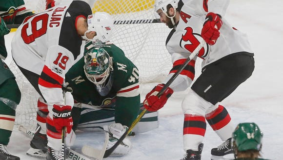 Minnesota Wild goalie Devan Dubnyk, center, defends