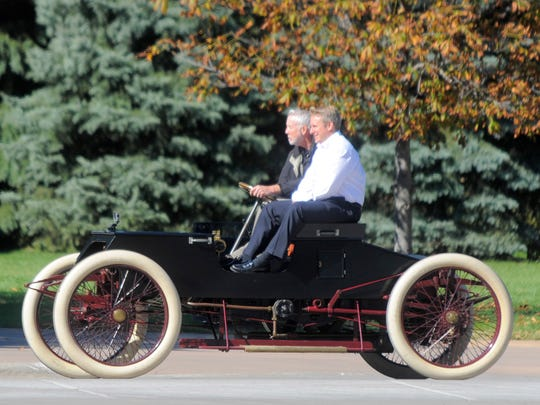 Greenfield Village mechanic Glenn Miller, takes Henry Ford III for a short drive in Henry Ford's 1901 Sweepstakes race car at Greenfield Village.