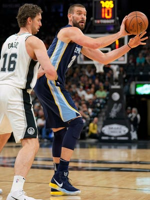 Memphis Grizzlies' Marc Gasol, right, looks to pass as he is guarded by San Antonio Spurs' Pau Gasol during the first half of an NBA basketball game, Wednesday, Nov. 29, 2017, in San Antonio.