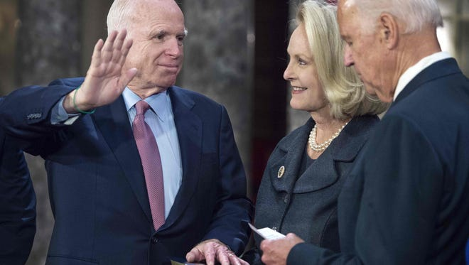 Sen. John McCain, R-Ariz., takes part in a ceremonial swearing-in by Vice President Biden as Cindy McCain holds the Bible during on Jan. 3, 2017.