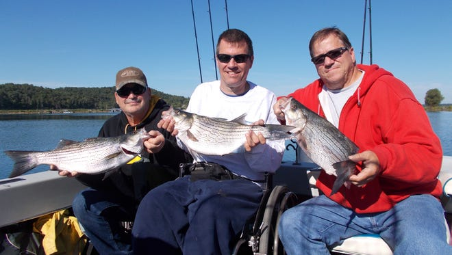 Lifelong friends Chuck, Greg and Russell show off their catch during a productive trip fishing for stripers on Norfork Lake.