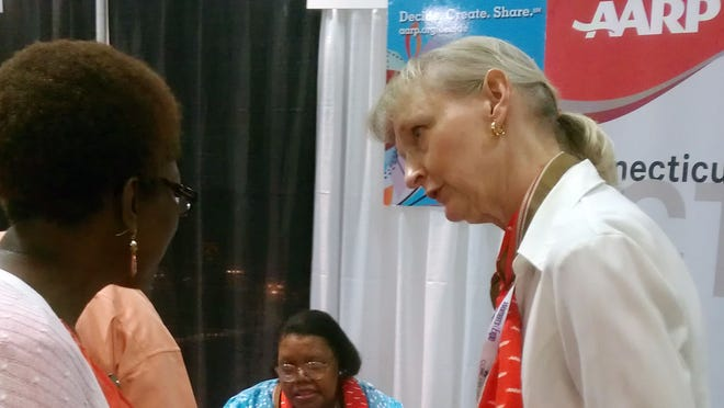An AARP volunteer speaks to a customer at the Connecticut Women's Expo on Sept. 7 in Hartford, Conn.