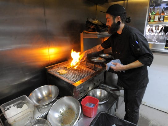 Sous chef Nick Taube prepares sardinas asadas at Midtown's
